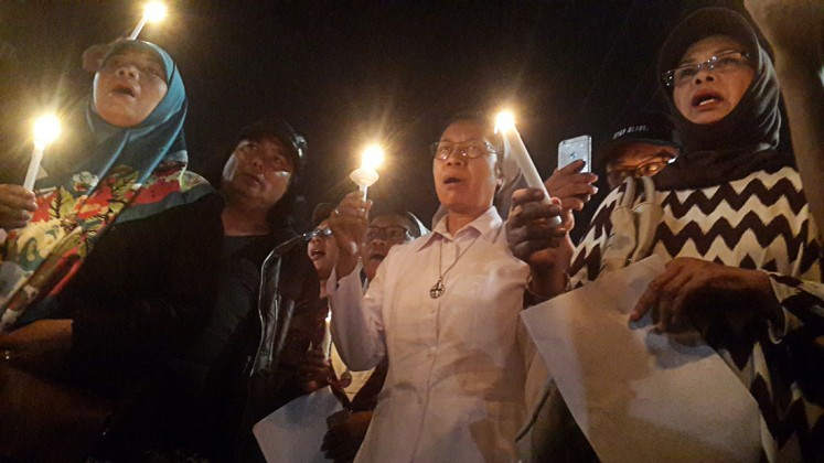 Remembrance: Yogyakarta residents and religious leaders attend a candlelight vigil at Tugu Monument, Yogyakarta, following suicide bombings in Surabaya, East Java, on May 13.