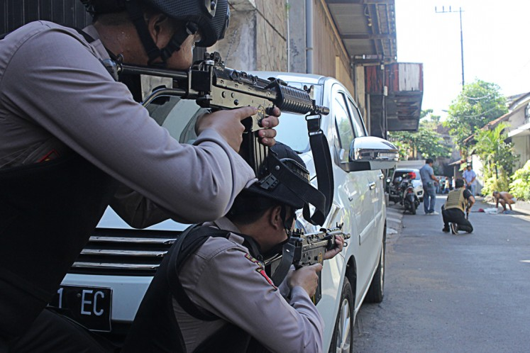 On alert: Police officers stand guard in areas around Jl. Niaga Samping following a bomb blast at the Surabaya Police headquarters in Surabaya, East Java, on May 14.