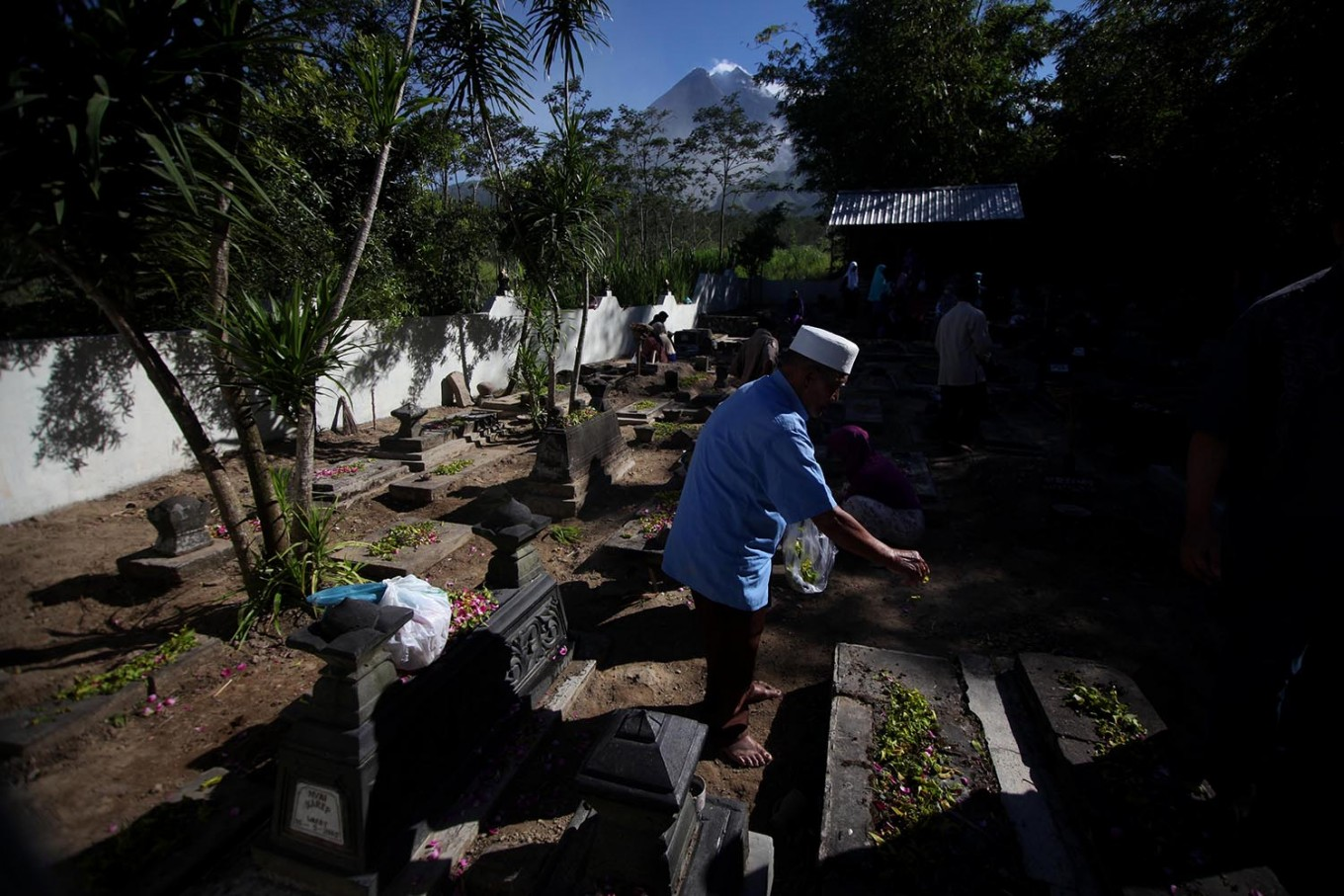 A man scatters rose petals on top of his relative's grave. JP/Boy T. Harjanto