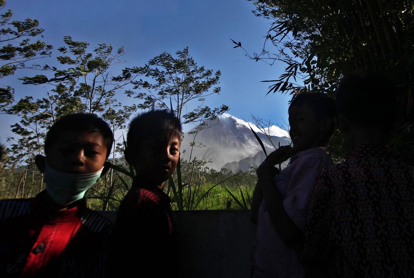 Three children play at the cemetery with Mount Merapi visible in the background. JP/Boy T. Harjanto