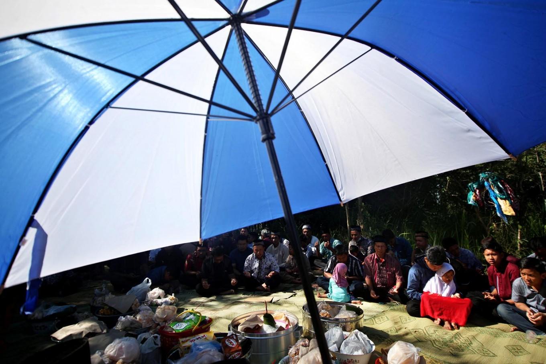 Villagers share food after praying. [JP/Boy T. Harjanto