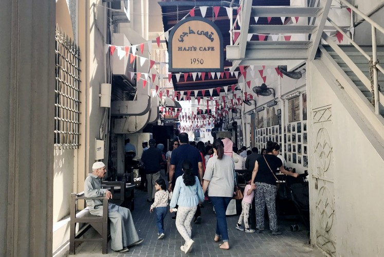 Gather round: Visitors flock to the alleyway in Manama Souq in which Haji Café is located.