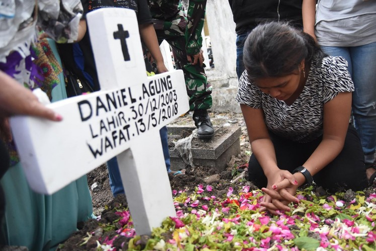 Novi, the sister of Daniel Agung Putra Kusuma, 14, prays at her brother's grave at the Putat Gede cemetary in Surabaya on May 15. Daniel was a victim of a suicide bombing at Surabaya Pentecostal Church (GPPS) on May 13.