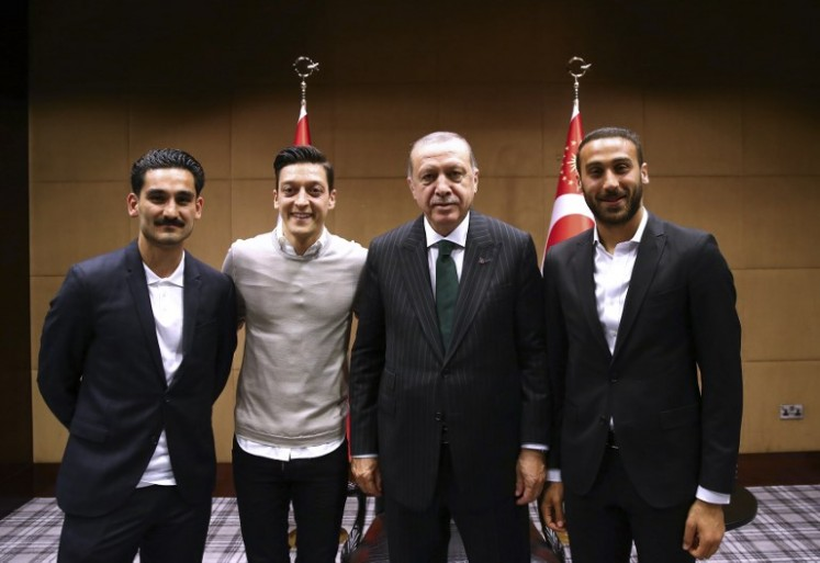 This handout picture taken and released on May 13, 2018 and released on May 14, 2018 by the Turkish Presidential Press office shows Turkish President Recep Tayyip Erdogan(second right) posing for a photo with Turkish football players Ilkay Gundogan (left), Mesut Ozil (2nd left) and Cenk Tosun (right) in London.