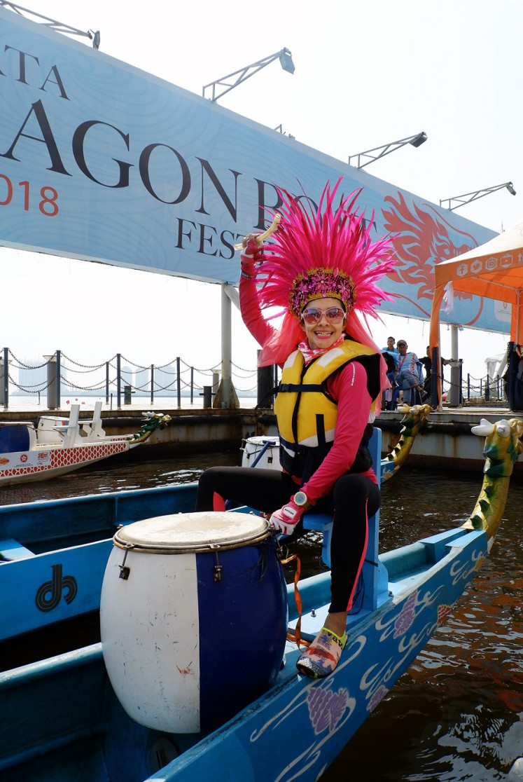 Let's rock: The captain of a dragon boat team wears an eye-catching pink feather headdress.