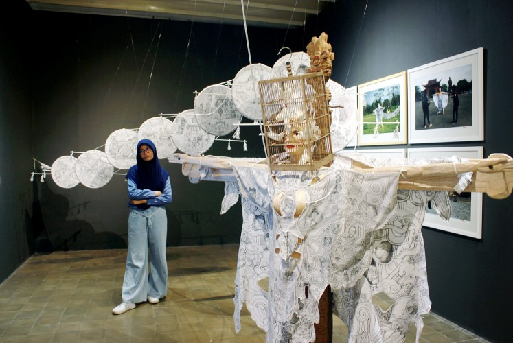 Fly me to the sky: A woman looks at an art installation by Kexin Zhang from China, who uses traditional Chinese kites in the artwork.