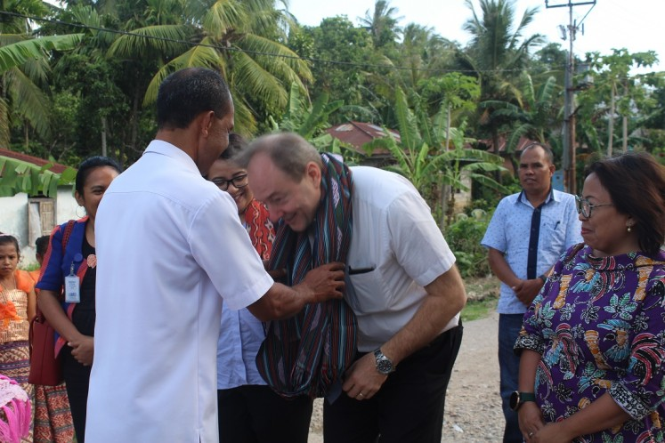 Warm welcome: Hans Farnhammer, the European Union's head of cooperation in Indonesia (right), gets traditional hand woven fabric from Buraen subdistrict head Jhon Nomeni during a visit to Buraen subdistrict, Kupang, East Nusa Tenggara, on Wednesday.