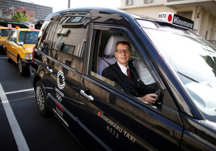 Wolfgang Loeger from Austria, a taxi driver of Hinomaru Kotsu Co., poses for a photograph inside a 'JPN Taxi' car, developed by Toyota Motor Co., in Tokyo, Japan May 14, 2018.