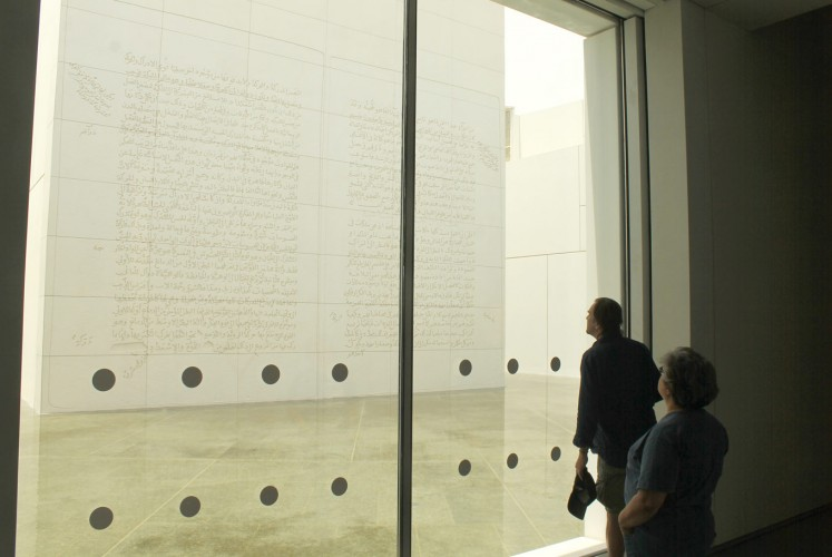Watch and wonder: Visitors admire American visual artist Jenny Holzer's limestone relief emblazoned with three pages of Arabic script, made in 2007. In the amphibious museum, the relief's foundation stands on seawater.