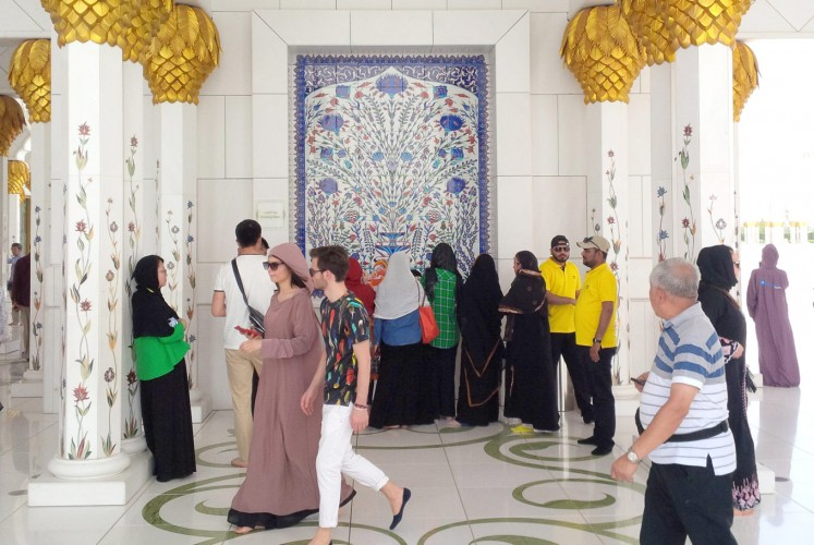 Just passing by: Visitors walk through the Sheikh Zayed Grand Mosque's hallway area, which is decoration and designed to evoke a Persian influence. At the center, thirsty guests line up to drink from a fountain water.