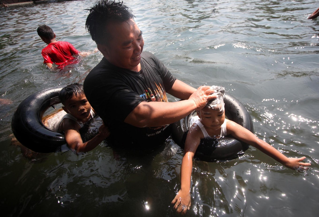 A father washes his son's hair to complete the Padusan ritual. JP/Boy T. Harjanto
