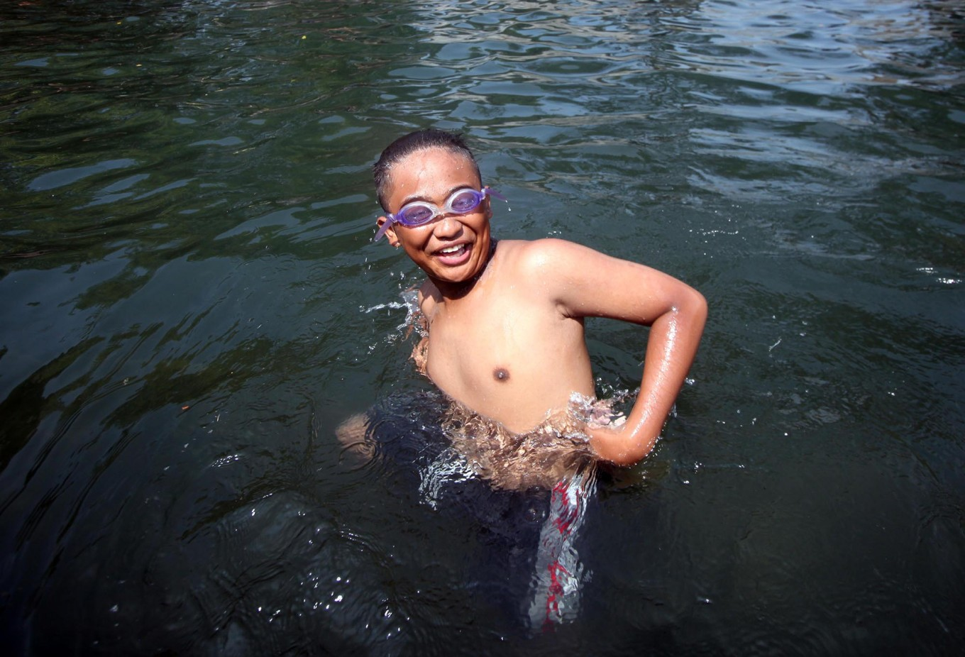 A boy wears goggles as he swims during Padusan. JP/Boy T. Harjanto