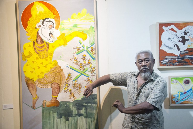 Puppet show: Otok Bima Sidarta poses next to his painting, titled Dibawah Kekuasaan Gareng (Under Gareng's Rule).