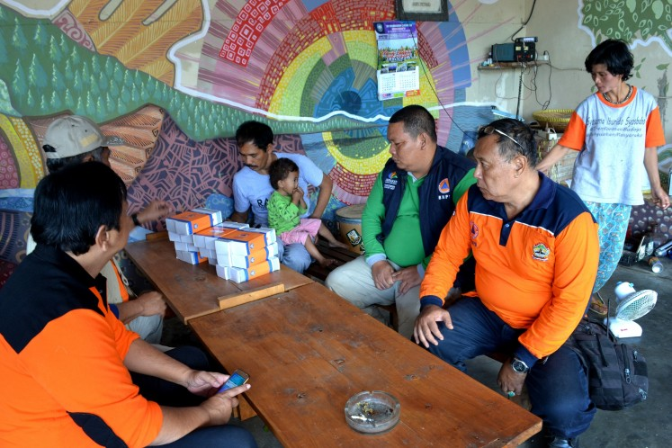 Sukiman Mohtar Pratomo (in grey shirt) is the head of the radio station. He can be seen here coordinating with the Magelang Disaster Mitigation Agency on the latest updates on Mount Merapi eruptions.