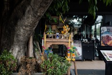 A spirit house is placed under a tree in front of a restaurant in Chiang Mai, Thailand. JP/Anggara Mahendra