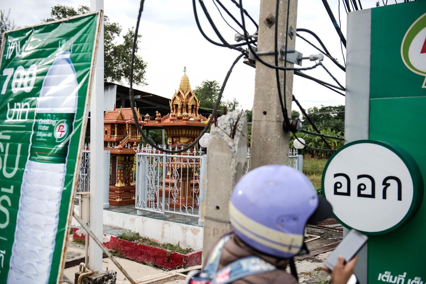 A spirit house is located underneath a billboard in Ayutthaya, Thailand. JP/Anggara Mahendra