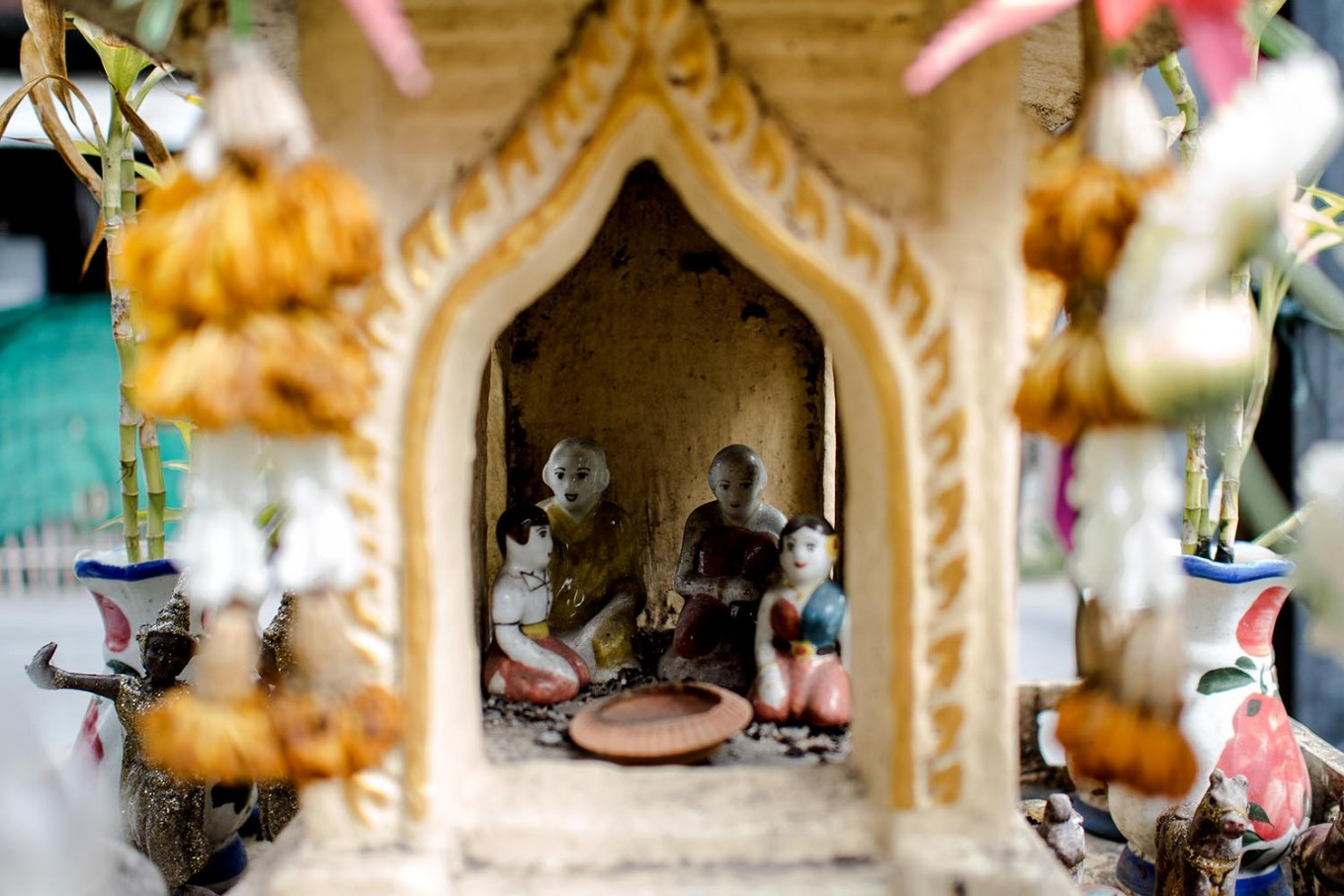 Small porcelain dolls inside a spirit house in Thailand. JP/Anggara Mahendra