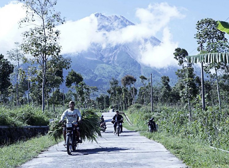 Daily routine: Residents carrying grass for their livestock pass a road in Tlogolele village, Selo district, Boyolali regency, Central Java, as thick smoke emanates from the crater of Mount Merapi.