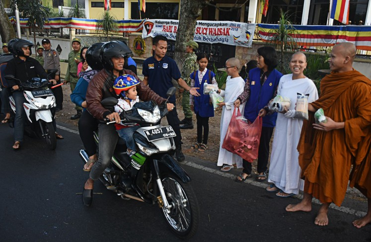 Motorcyclists passing the Dammadipa Arama Vihara on Jl. Raya Ma, Batu, Malang, East Java, get packages of sugary delicacies for breaking the fast, known locally as 'tajil', from Buddhist monks during the celebration of Vesak on Tuesday.