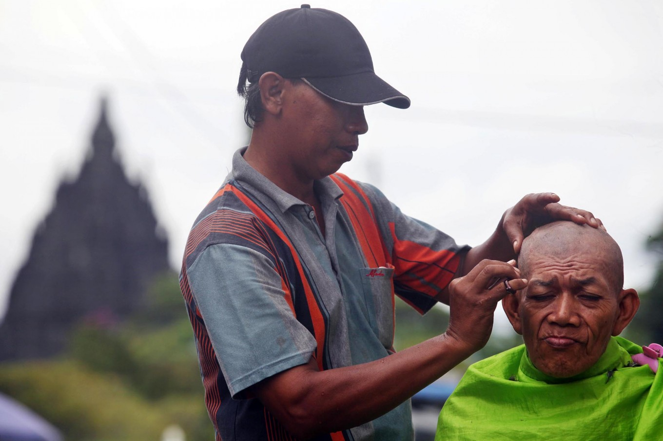 nice view: Widodo cuts the hair of a customer against the backdrop of the Prambanan temple. JP/ Boy T Harjanto