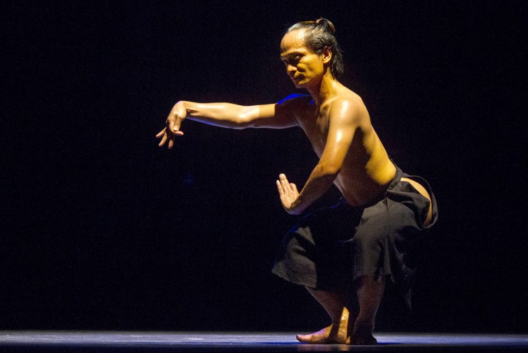 In the dark: Riyanto combines modern and traditional dance movements, as well as masculine and feminine gestures in his dance.