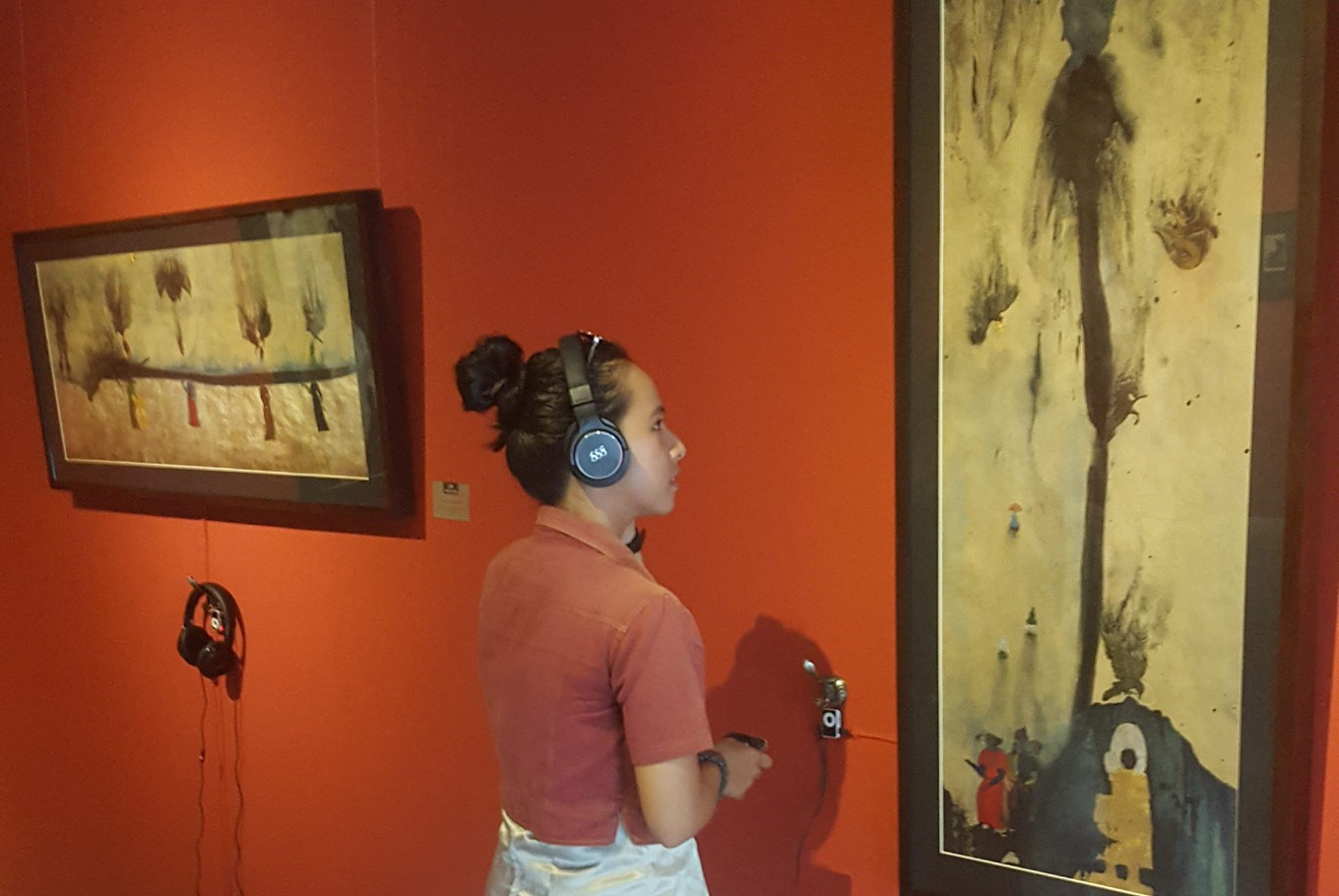 A visitor to the exhibition engages with Amin Taasha's work while listening to an audio composition by Vanja Dabic.