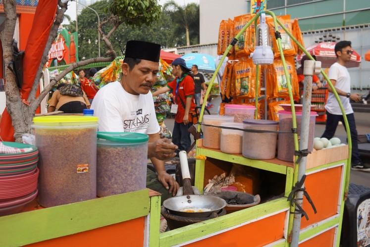 A seller cooks 'kerak telor' at the 2018 Jakarta Fair.