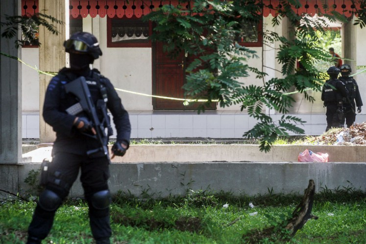Police officers stand guard in front of a student facility building in Riau University in Pekanbaru, Riau province on June 2. Students and alumni often spend the night in such buildings.