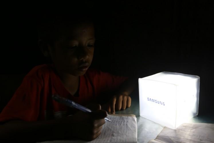 A boy studies beside a solar-powered lantern.
