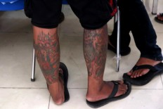 Inked: Numerous patterns and illustrations of tattoos are featured on a man's legs. JP/Maksum Nur Fauzan
