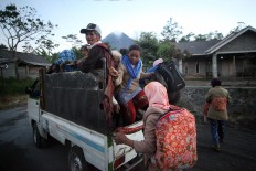 Villagers from Cangkringan district, Sleman regency, Yogyakarta, flee their homes on a pick-up truck on Tuesday, May 22, 2018. JP/Boy T. Harjanto