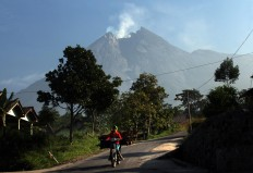 Mount Merapi spews smoke while a villager is seen carrying wood. JP/Boy T. Harjanto
