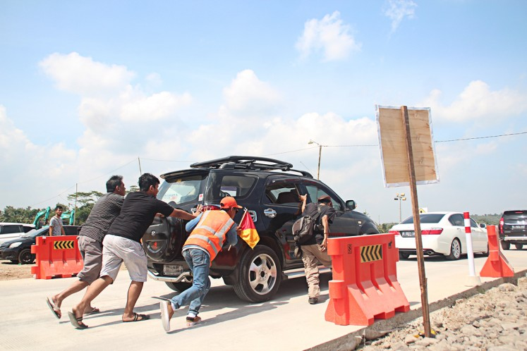 A stalled vehicle is pushed on the Salatiga-Kartasura functional toll road on June 11.