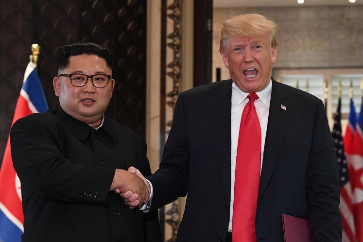 US President Donald Trump (right) and North Korea's leader Kim Jong Un shake hands following a signing ceremony during their historic US-North Korea summit, at the Capella Hotel on Sentosa island in Singapore on June 12.