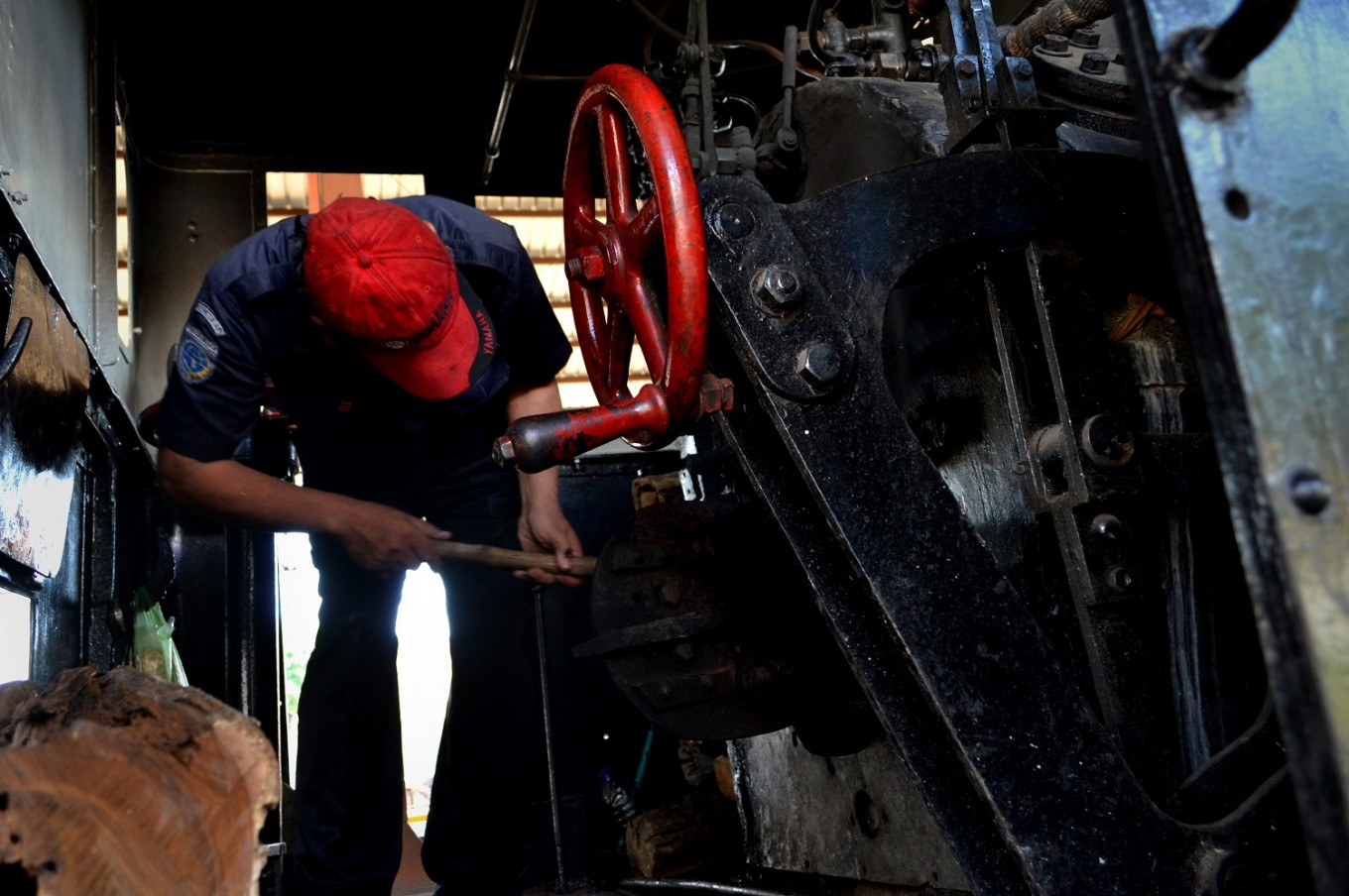 The engineer checks the locomotive's boiler prior to departure.