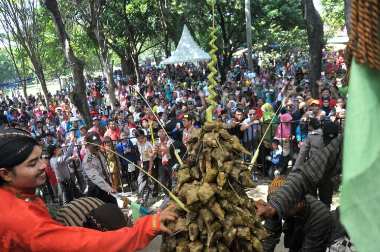 Thousands of people eagerly wait to receive 'ketupat' (rice cake) in the Grebeg Syawal ritual at Solo Zoo, Surakarta, Central Java.