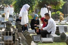 Families visit the graves of their loved ones at Sirnaraga Public Cemetary in Bandung, West Java on June 15, 2018. Many Muslims visit the cemetery after attending Friday prayers. JP/Arya Dipa