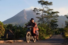 A couple in Balerante, Kemalang, Klaten, Central Java ride a motorcycle to Al Qodar Mosque for prayers on June 15, 2018. The residents of Balerante live only 3.5 kilometers from the peak of Mount Merapi, an active volcano that has experienced several phreatic eruptions recently. JP/Magnus Hendratmo