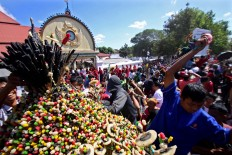 People race to get snacks from the gunungan (cone-shaped offering) during a procession of Grebeg 1 Syawal 1439, a tradition at the Gedhe Mosque in Kauman, Yogyakarta on June 15, 2018. The gunungan symbolizes alms given by the Sultan of Yogyakarta to residents. The kraton made seven gunungan for the residents. JP/Aditya Sagita