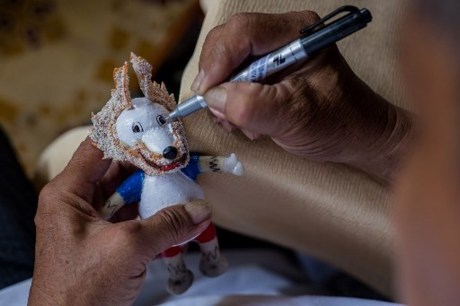 This picture taken on June 20, 2018 shows retired Vietnamese English teacher Nguyen Thanh Tam assembling eggshells as he creates a model of Zabivaka, the 2018 Russian World Cup mascot, at his home in Ho Chi Minh City.