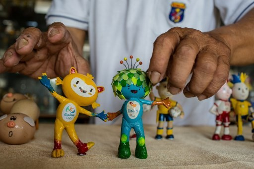 Nguyen Thanh Tam displaying two finished models of Vinicius, the 2016 Rio Olympics mascot, made from eggshells, at his home in Ho Chi Minh City.