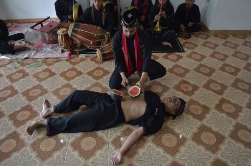 This picture taken on February 4, 2018 shows Indonesian debus master Aris Afandi (C-top) cutting watermelon on the stomach of his colleague during a skills demonstration in Bandung.