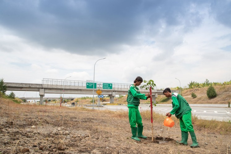 Planting saplings: Workers plant trembesi saplings on the side of a highway connecting Gempol district and Pasuruan regency in East Java.