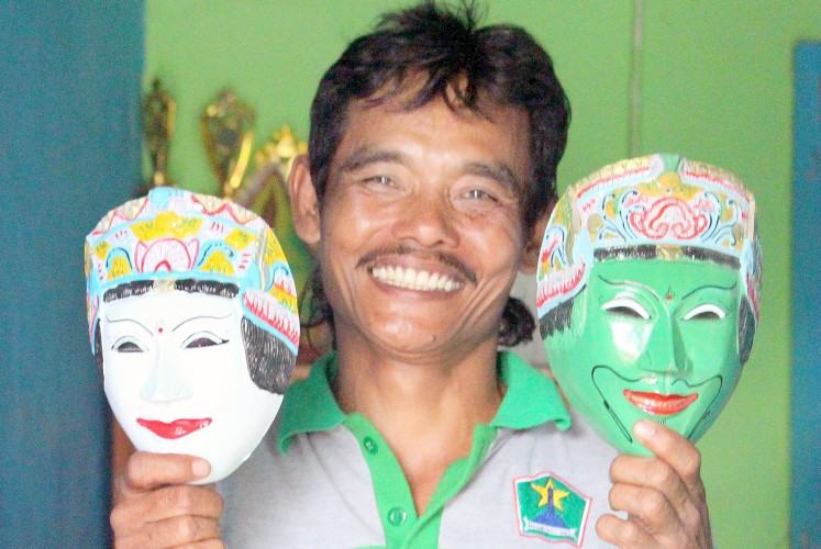 A display of craftsmanship: Mask artisan Prasetiyo Hadi poses with two masks at his shop in Kampung Topeng.