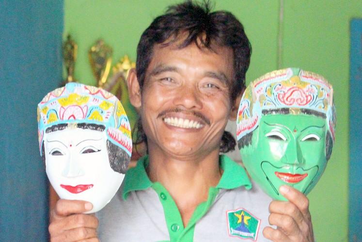 A display of craftsmanship: Mask artisan Prasetiyo Hadi poses with two masks at his shop in Kampung Topeng.