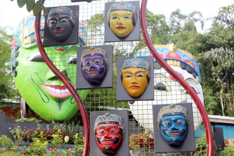 Many faces: Small masks are put on display in front of Panji Asmara Bangun and his wife Dewi Sekartaji in Kampung Topeng.