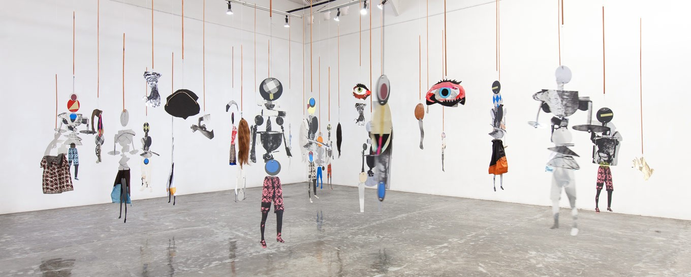 A wider angle shows suspended puppets in 'The Choreography of Cutting' by Sally Smart at the Tony Raka Art Gallery.