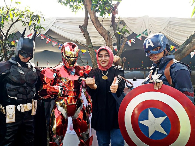Show your creativity: A voter takes a picture with election officials wearing costumes of Superheroes at polling station TPS 3 in Citarum subdistrict, Bandung, West Java, after casting vote for the West Java gubernatorial election on June 27.