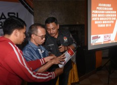 General Elections Commission (KPU) staff brief a blind voter on how to cast his vote on a braille ballot paper in Malang, East Java, during a simultaneous regional election familiarization session on Monday, June 25, 2018. JP/Aman Rochman