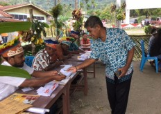 A voter collects a ballot paper from an election official wearing traditional Papuan dress, on June 27, 2018 at polling station TPS 005 in Awiyo subdistrict, Abepura district, Jayapura, to vote in the Papua gubernatorial election. JP/Nethy Dharma Somba